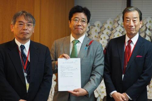 加藤勝信厚生労働大臣、吉田正樹様、 黒川清様の写真です。